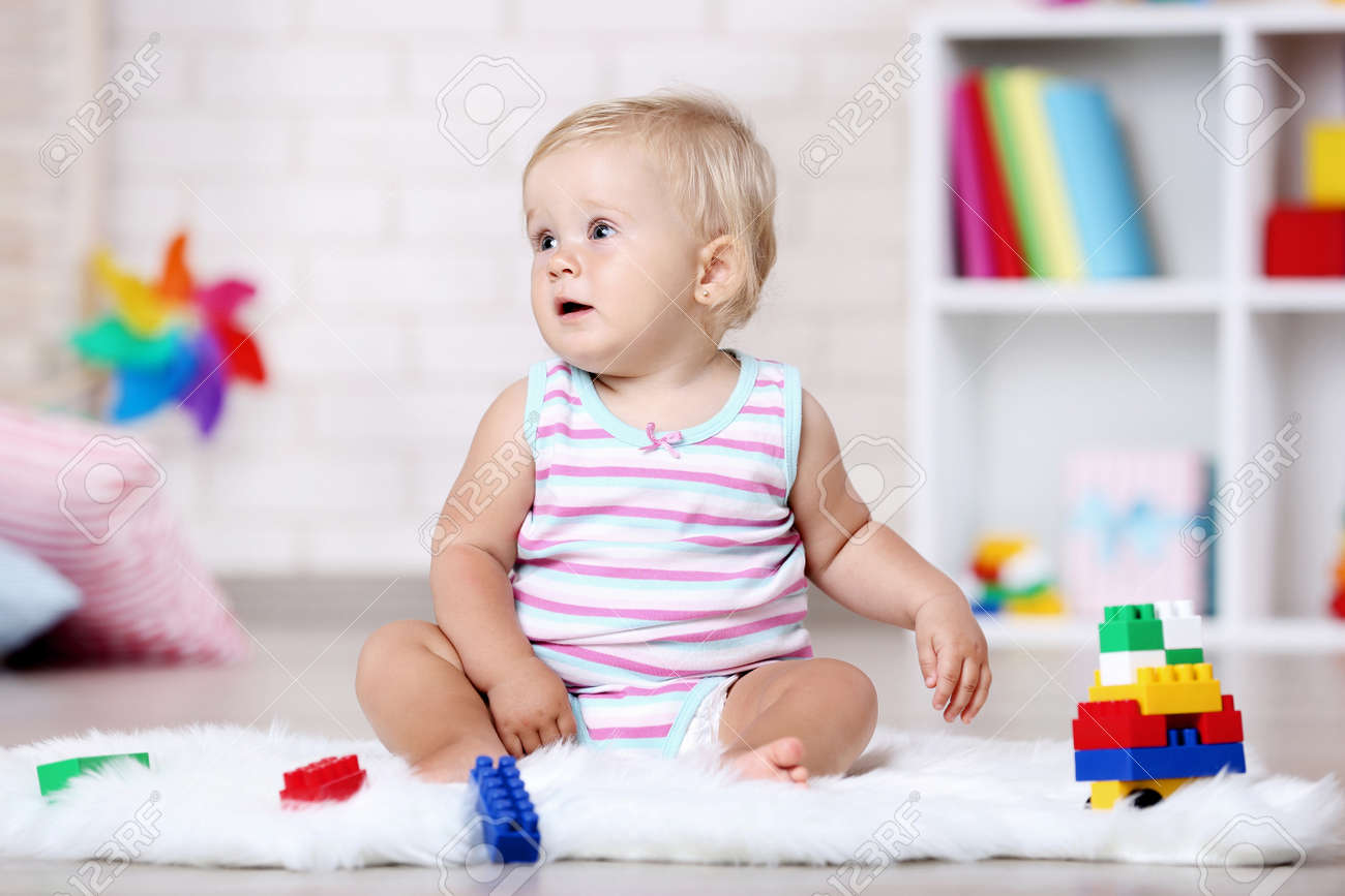 Baby girl sitting on white carpet with toys - 120768145