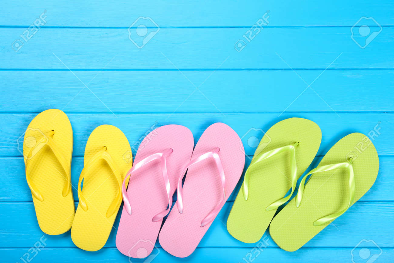 Pairs of colorful flip flops on blue wooden table - 121071830