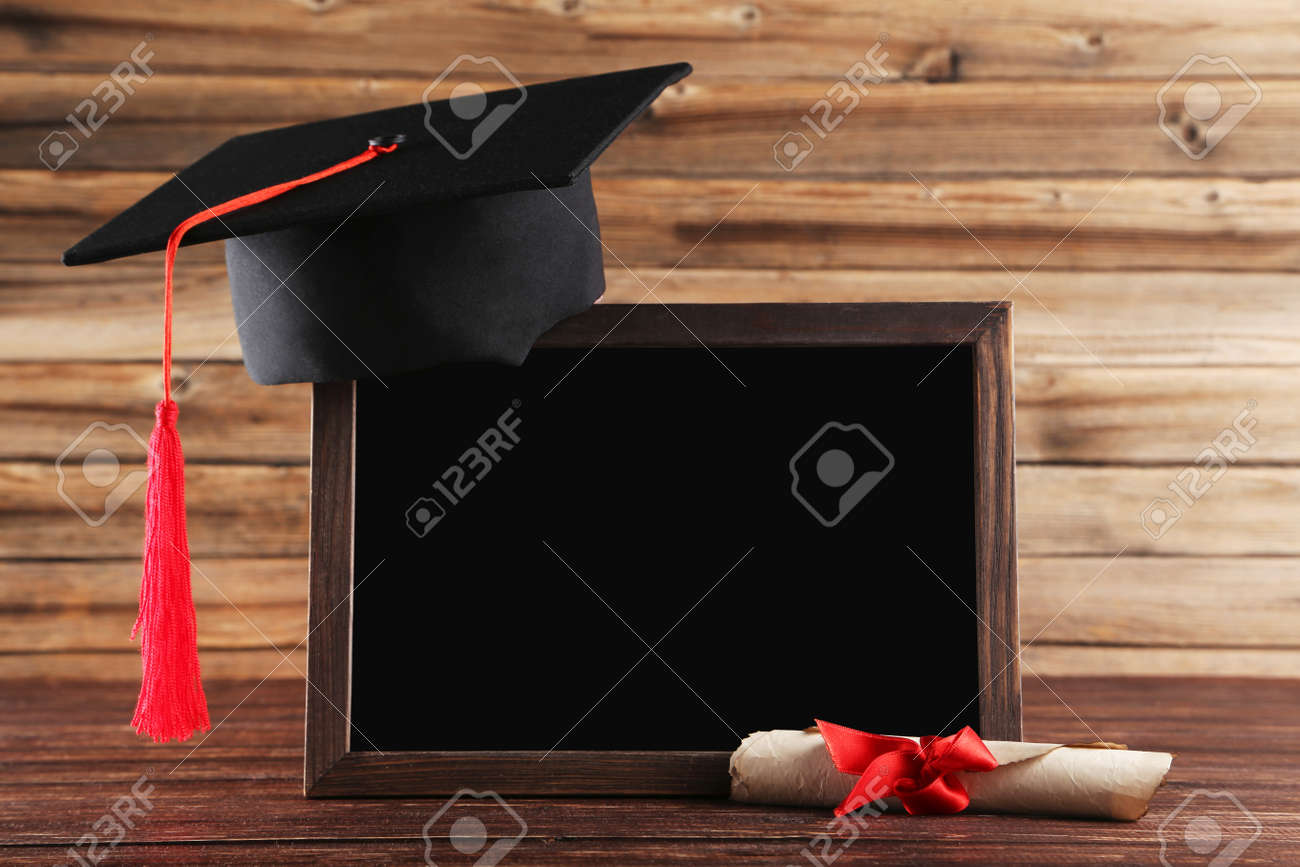 Graduation cap with diploma and blank frame on brown wooden table - 126161527