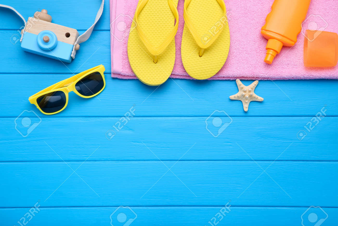 Fashion clothing with starfish and sunscreen on blue wooden table - 126161640