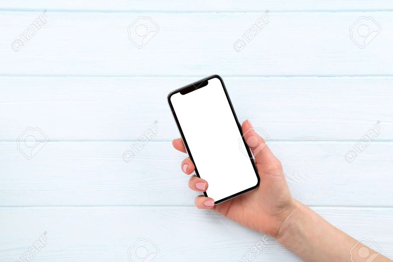 Smartphone in female hand on wooden background - 127094216
