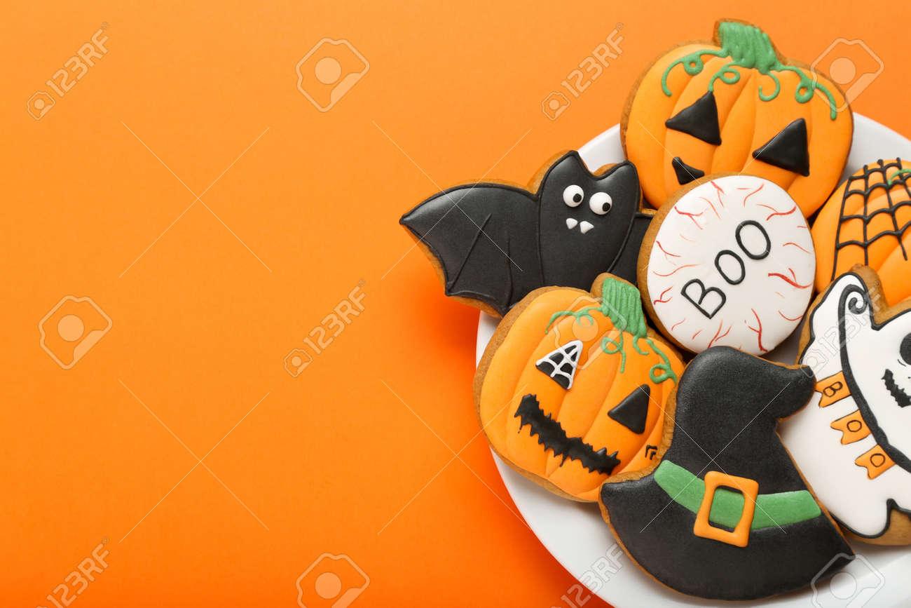 Halloween gingerbread cookies in plate on orange background - 129766045