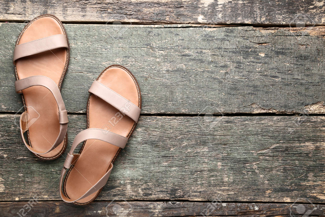 Female beige sandals on grey wooden table - 129976019