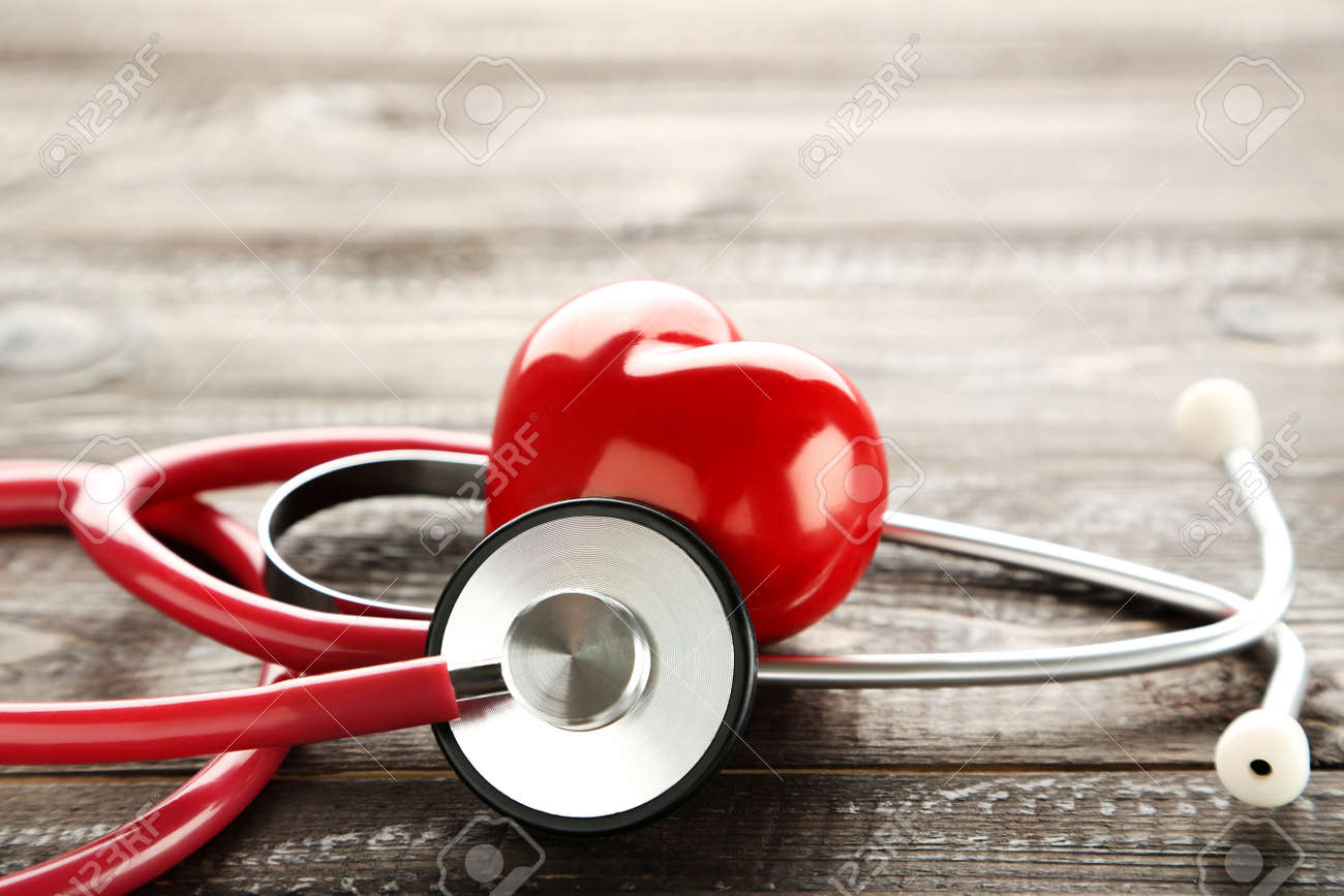 Stethoscope with red heart on brown wooden table - 143386568