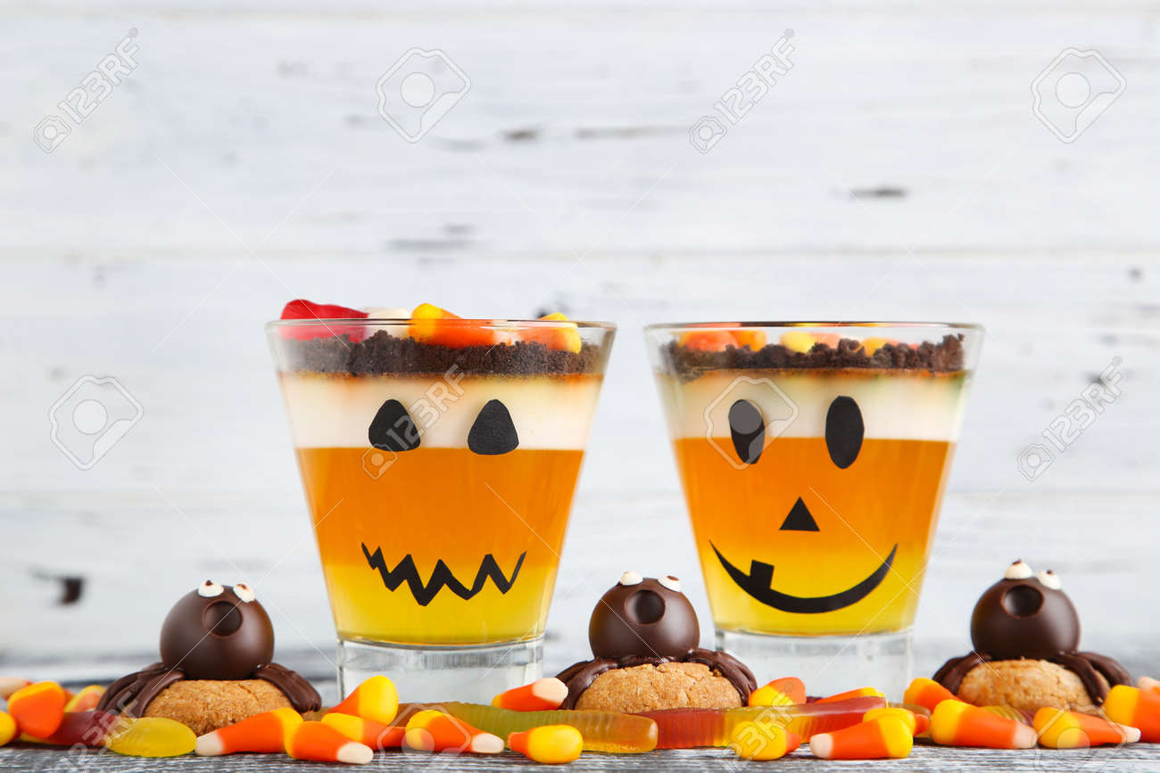 Halloween jelly in glasses with candies and cookies on wooden table - 157897638