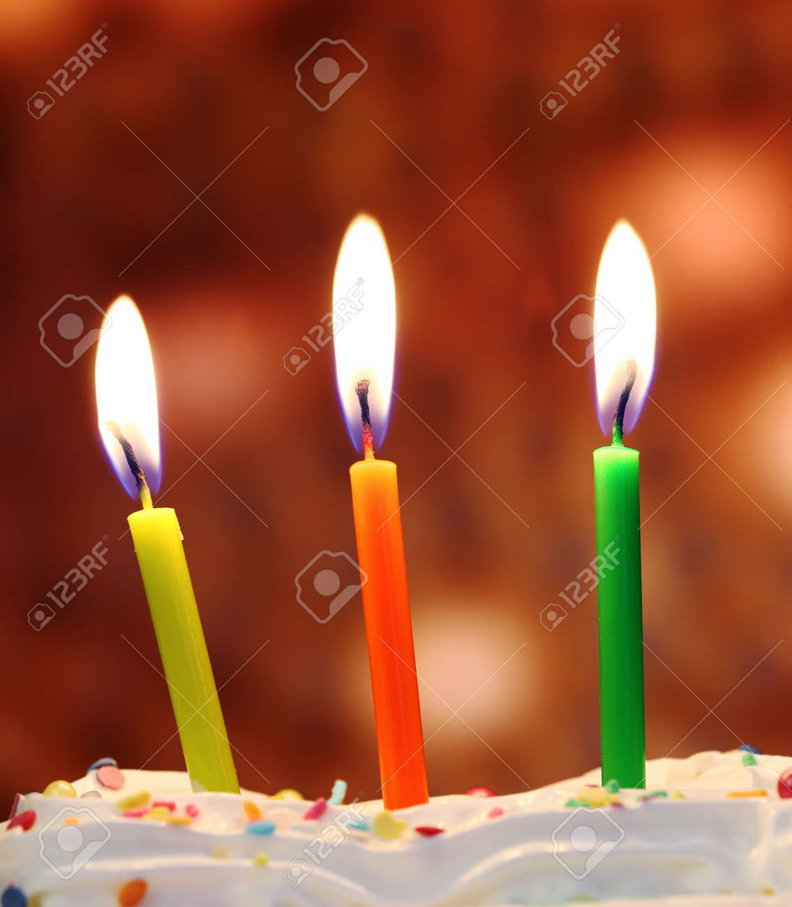 three lit birthday candles close up shallow dof stock photo