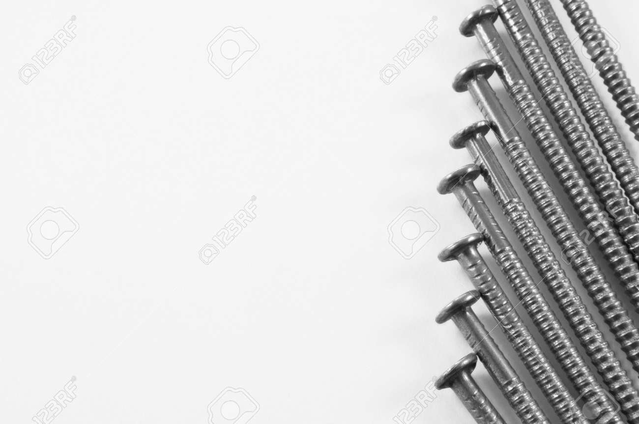 Close up, low level angle capturing steel ring shank nails arranged parallel and in the