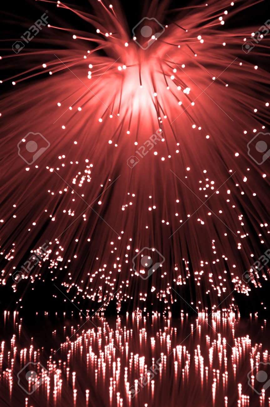 Many illuminated red fiber optic light strands cascading down and reflecting into the foreground. Black background Stock Photo - 9318625