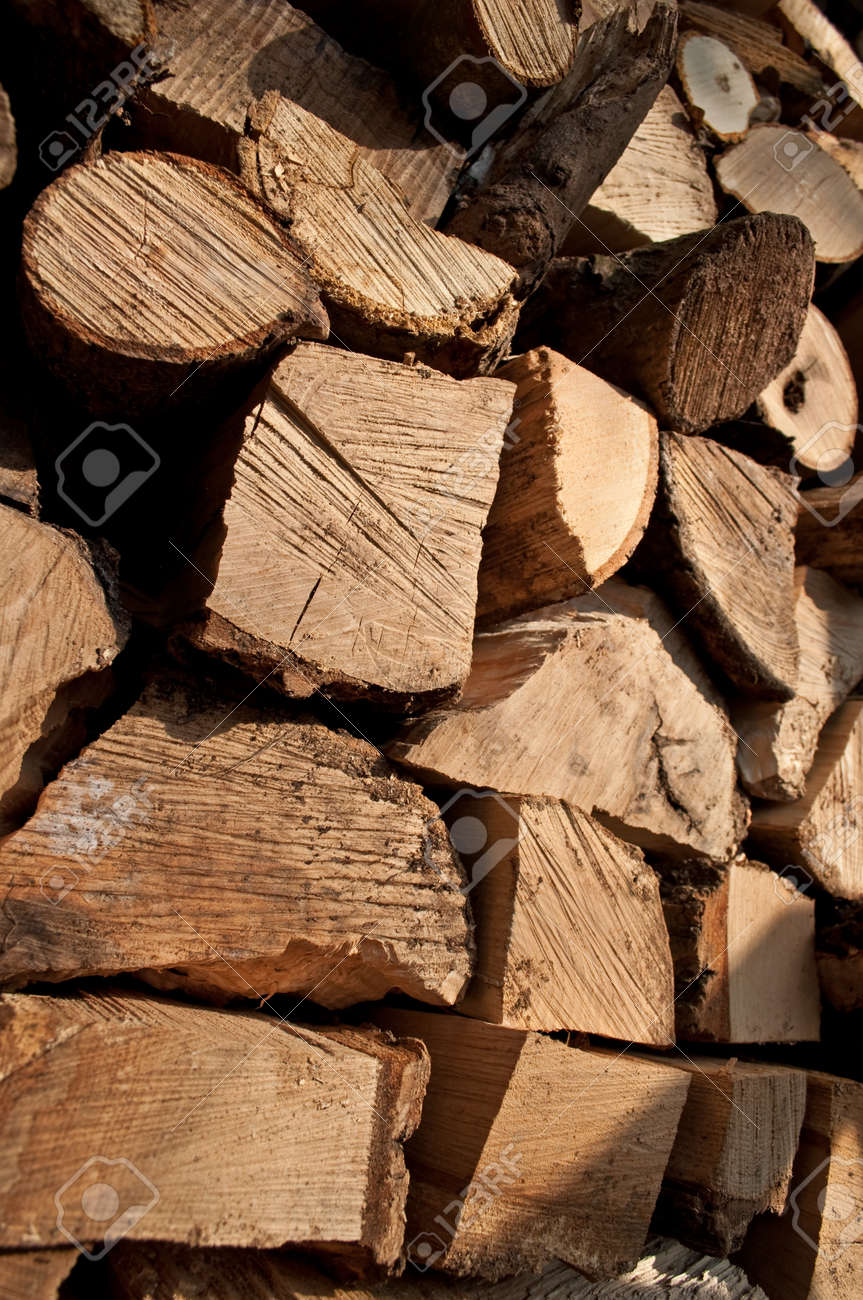 Close up on the ends of a large group of stacked, chopped rustic fire wood in outdoor setting with full sunlight Stock Photo - 9488457
