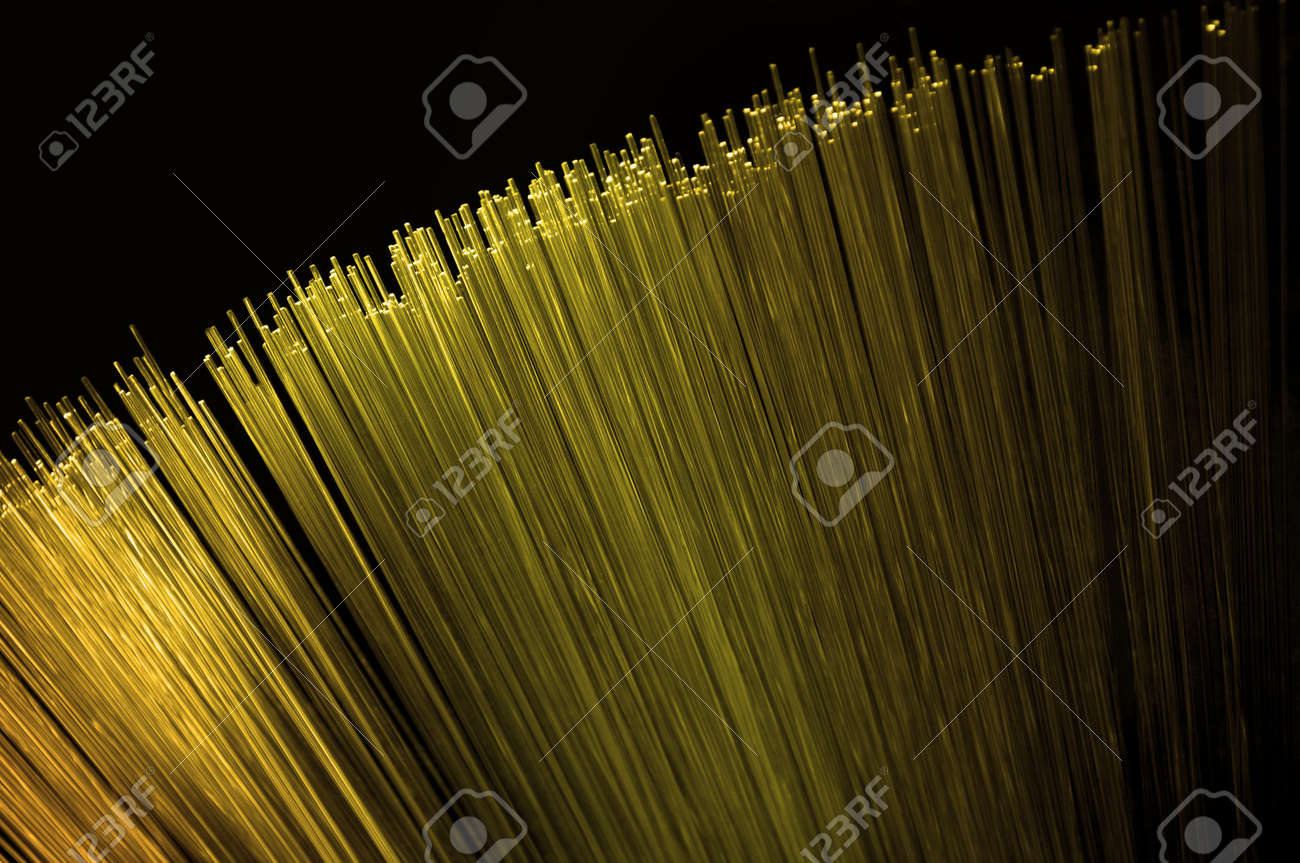 Close up on the ends of many illuminated golden fiber optic light strands arranged over black. Stock Photo - 10589107