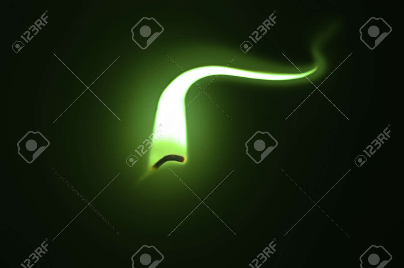 Close up on an ignited candle wick with extended green flame against a black background. Stock Photo - 11104566