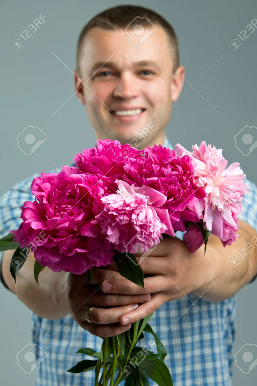 Greetings Close Up Of Smiling Man Giving Bouquet Of Flowers Stock ...