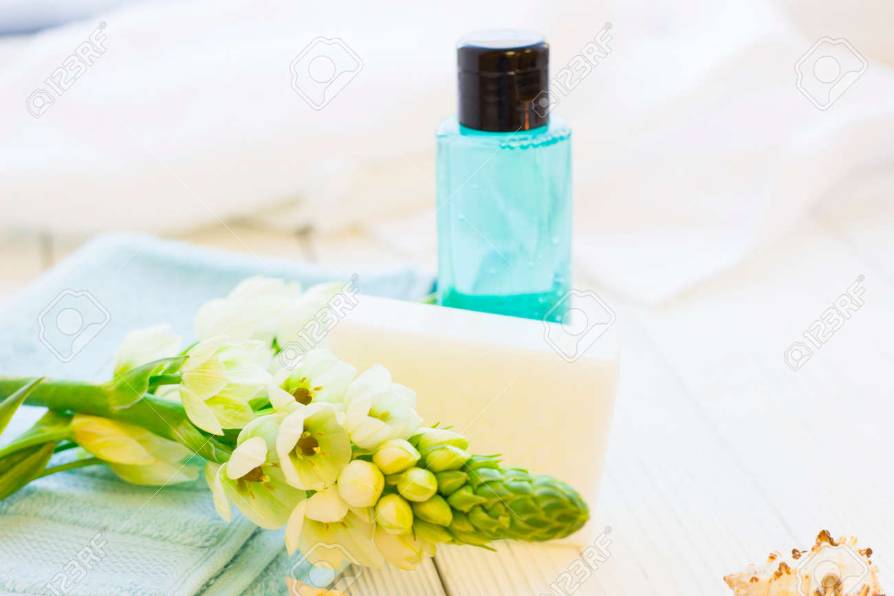 Spa Items Set With A White Flower Spur On A Blue Towel A Bar