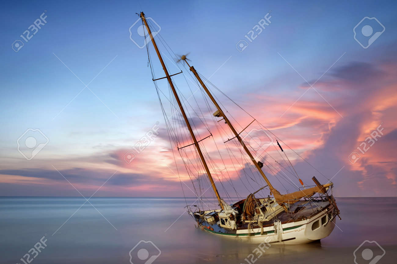 sailboat wreck in sea on the sand beach at sunset time Stock Photo - 42818525