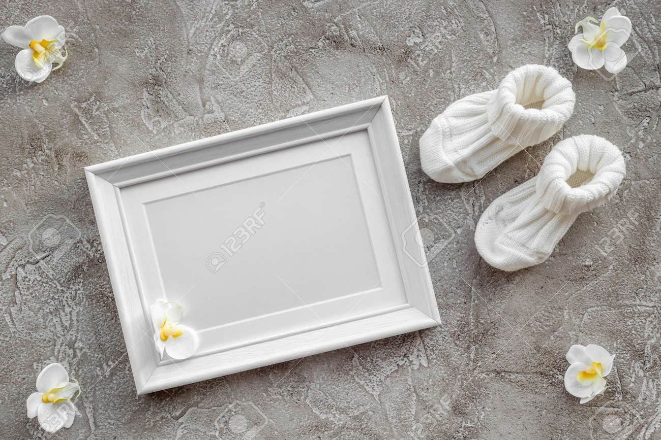 Baby Shoes And Frame For Baby Shower Design On Gray Stone Background