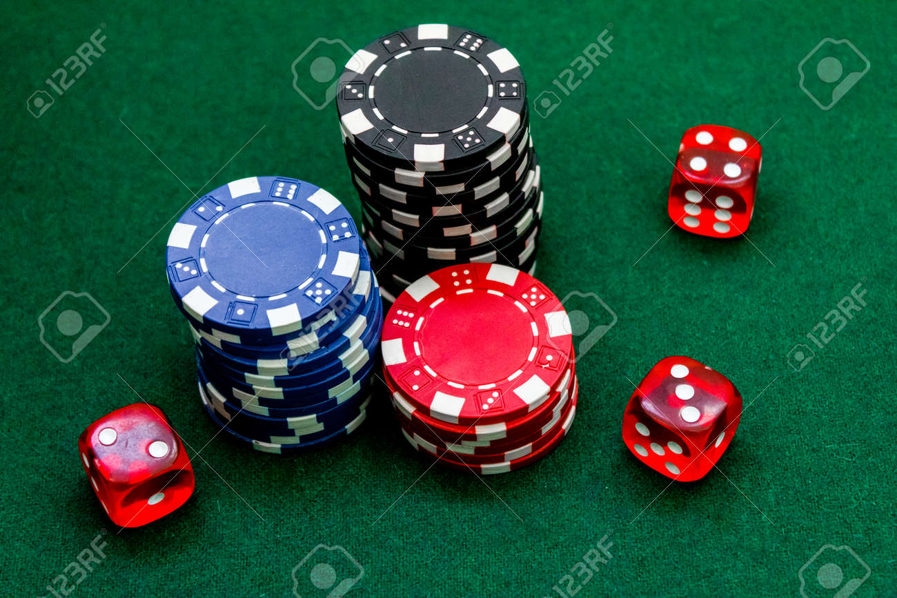 Poker Chips And Dice On A Green Gaming Table Top View Close Up Stock Photo