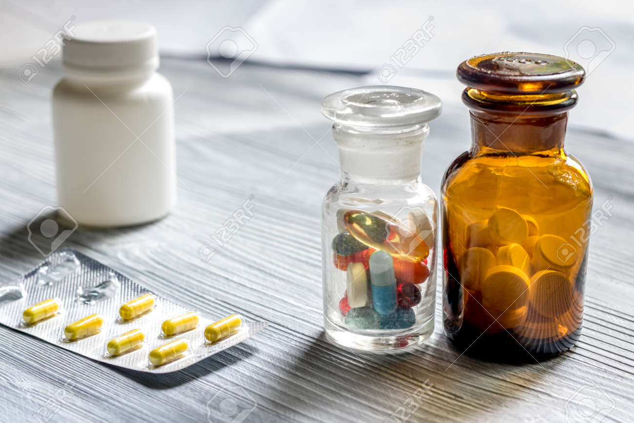 Vitamins And Supplements Pills And Pill Bottle On Grey Wooden