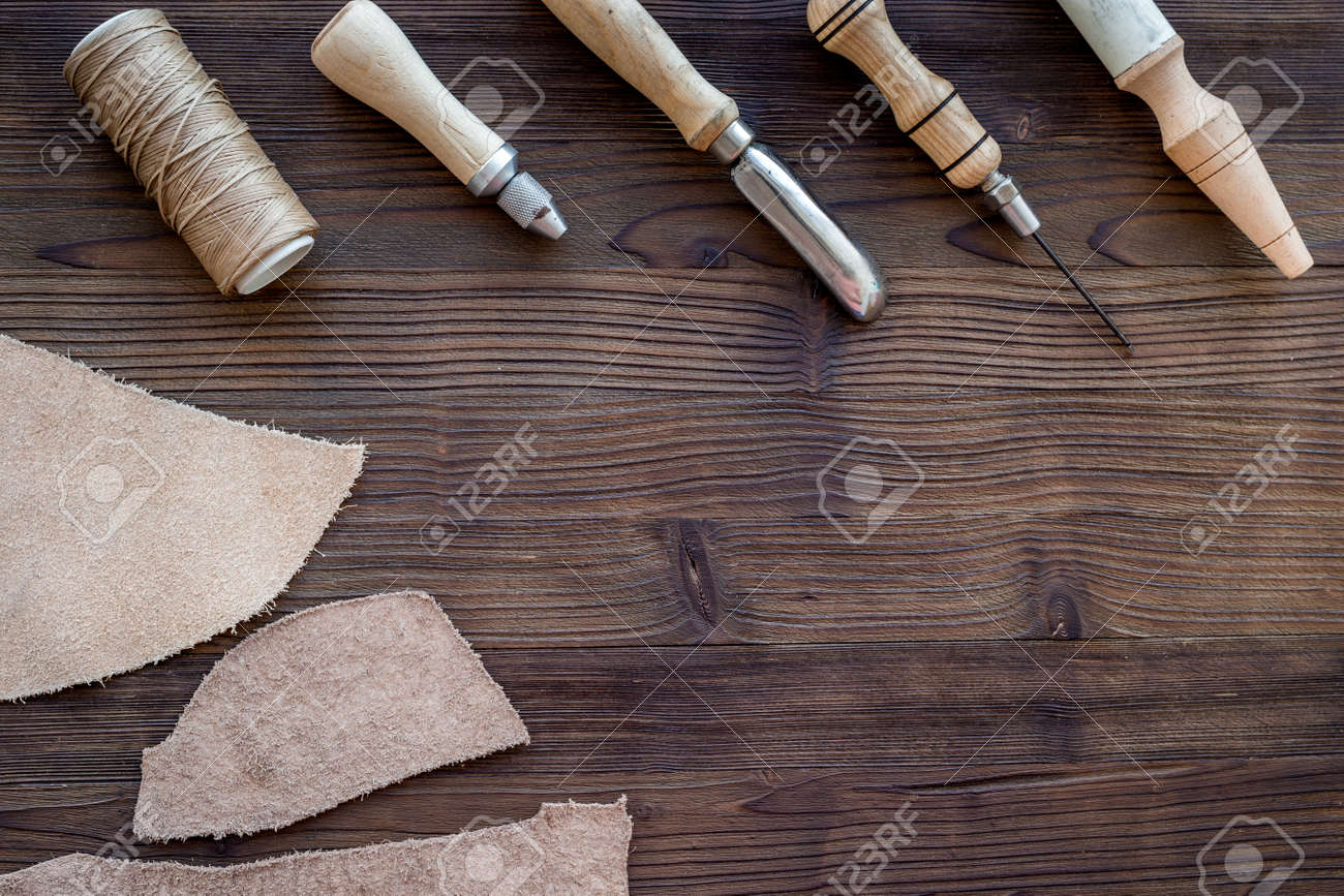Leather craft. Knife, awl and other tools on dark wooden background top view copyspace - 84046199