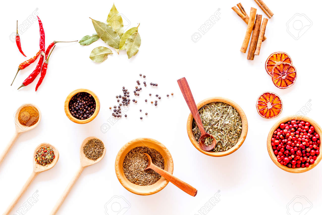 Kitchen table with spices and dry herbs on white kitchen desk..