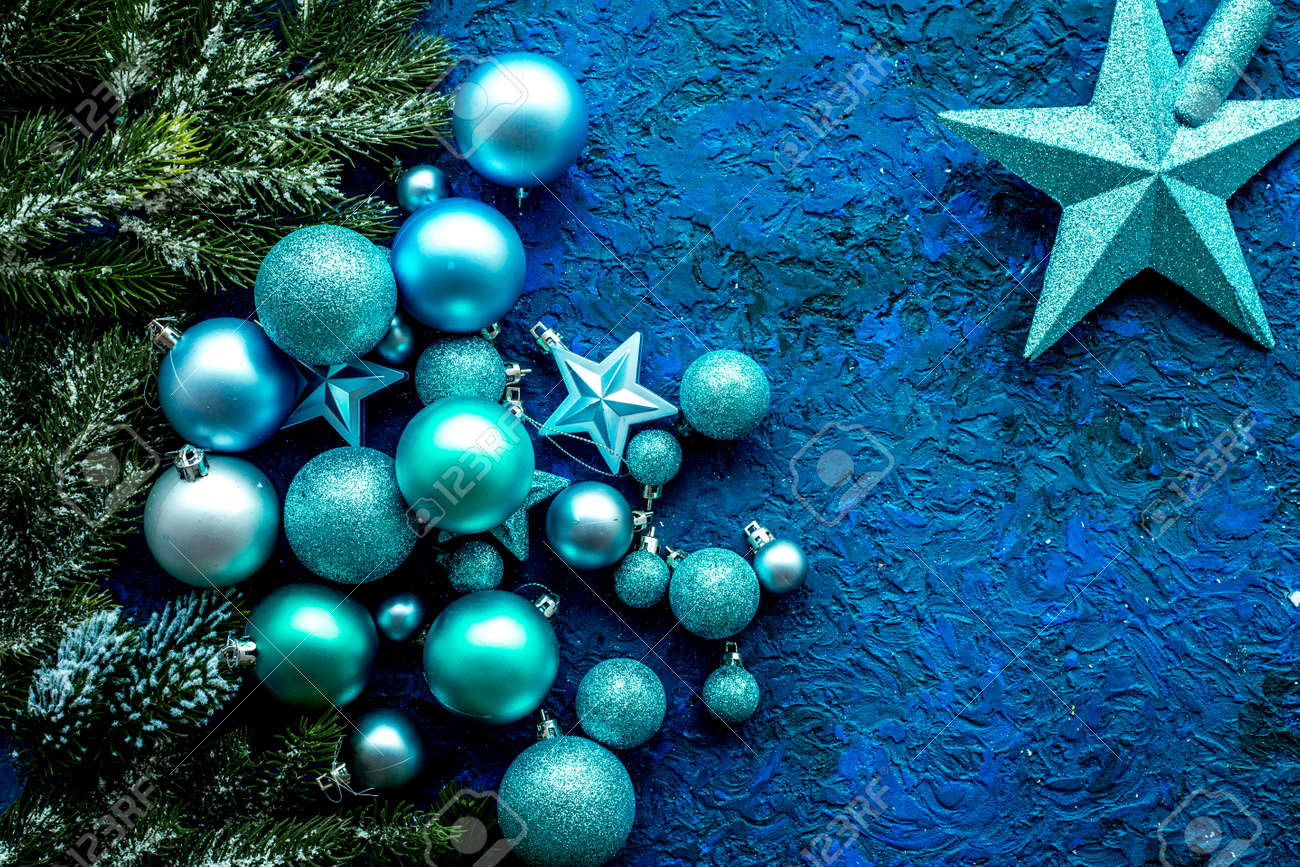 christmas tree decorations with balls and stars new year toys on blue background top view space