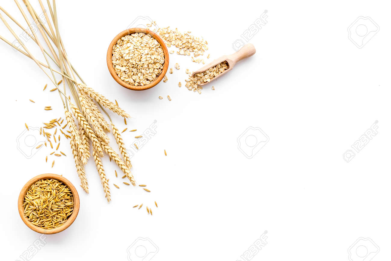 Oatmeal and oat in bowls near sprigs of wheat on white background top view. - 96270726