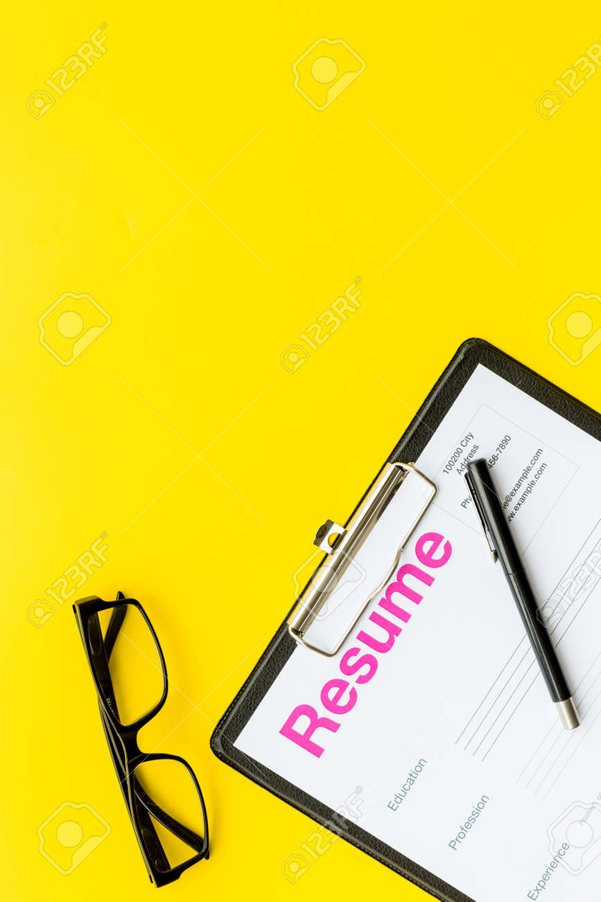 resume Pad Resume looking for work concept resume on pad near pen and glasses stock yellow background top