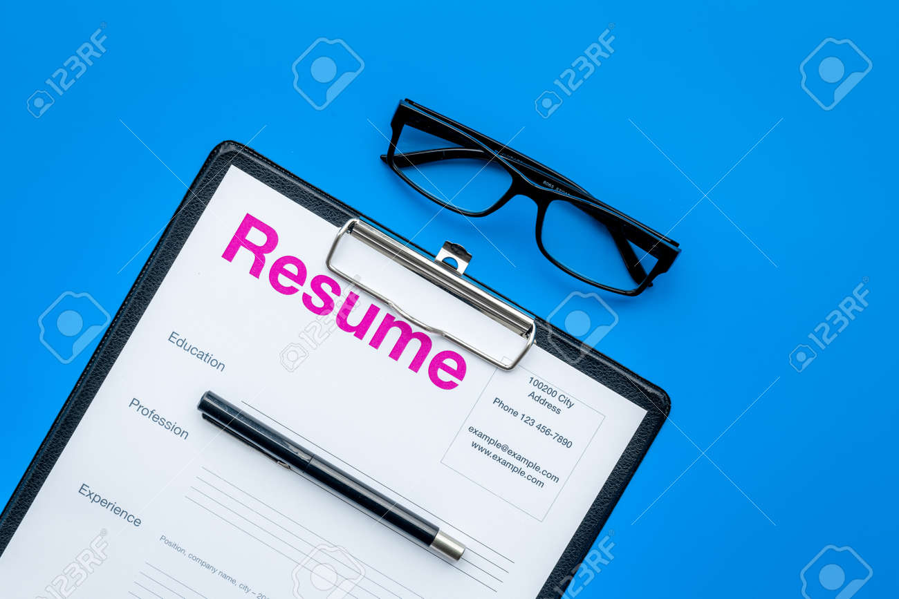 resume Pad Resume looking for work concept resume on pad near pen and glasses stock blue background top