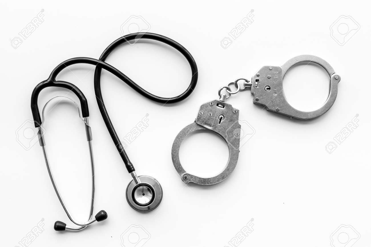 Medical lawsuit. Arrest for medical crime concept. Handcuff near stethoscope on white background top view. - 111360729
