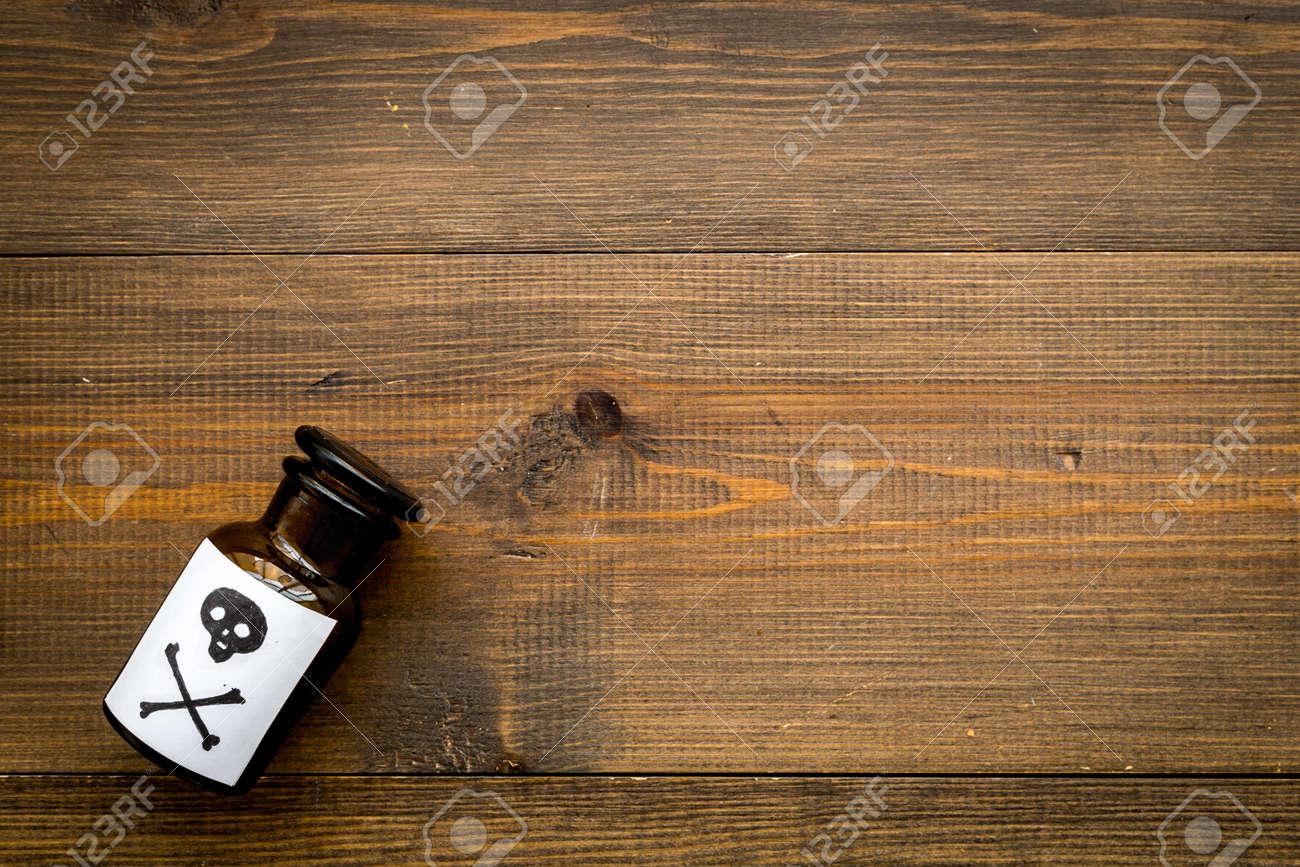 Bottle with skull and crossbones on dark wooden background - 112799506