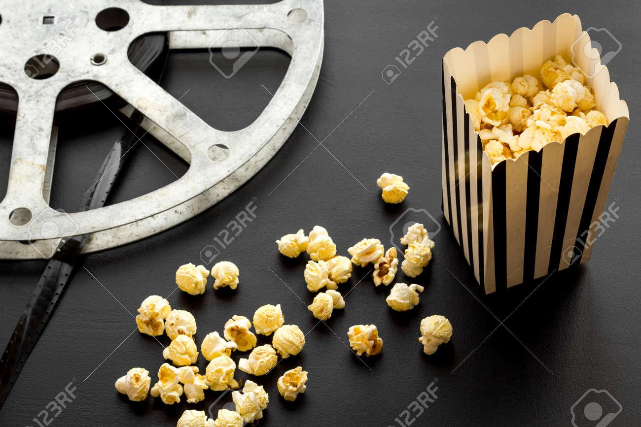 Cinema concept. film stock and popcorn on black background. - 116880229