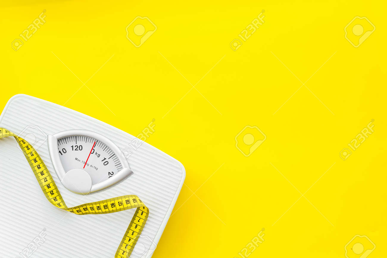 Diet. Bathroom scales and measuring tape for weight loss concept on yellow background top view mock up - 122365794