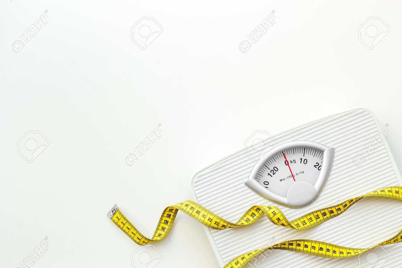 Diet. Bathroom scales and measuring tape for weight loss concept on white background top view space for text - 122458451