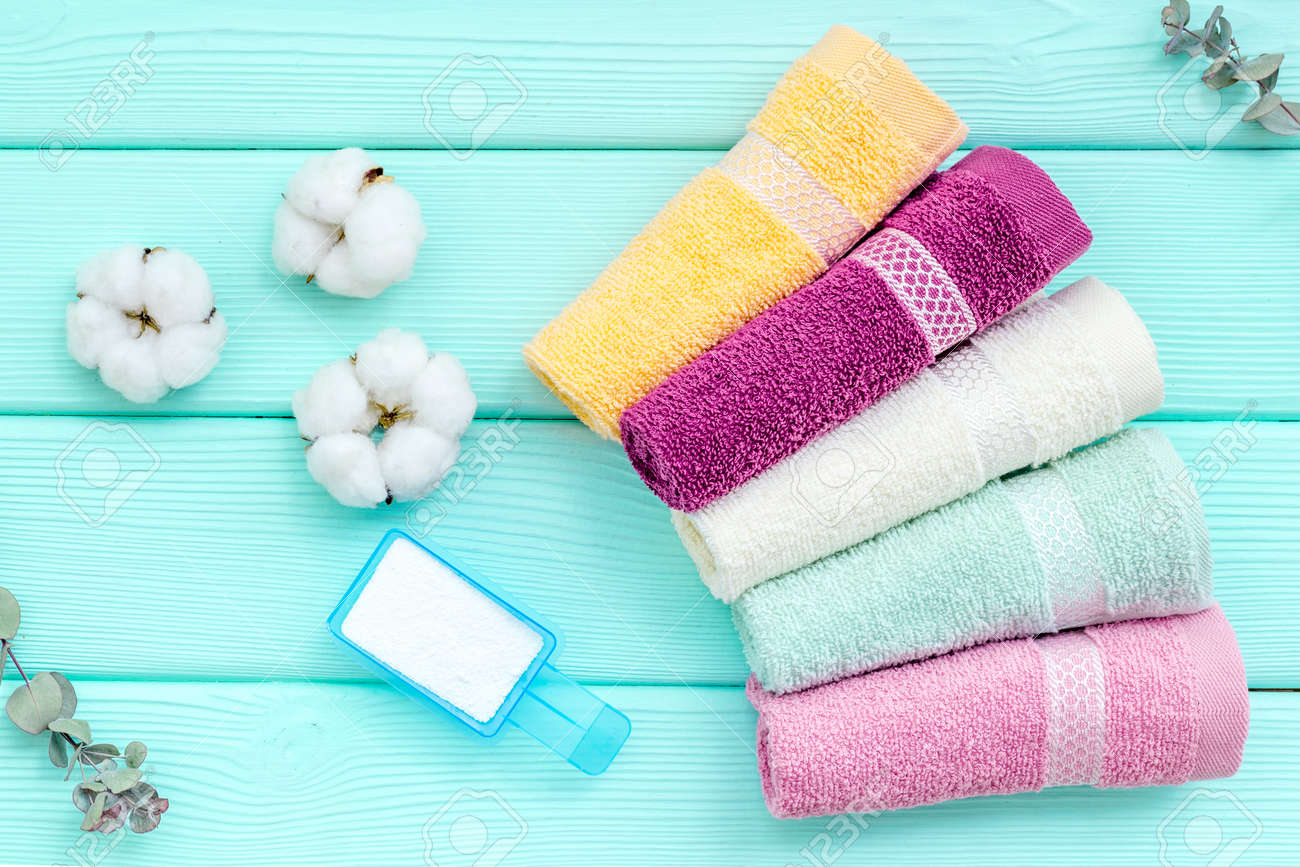 Products of cotton set. Preparing for laundry with washing powder and towels on mint green wooden background top view - 123808119