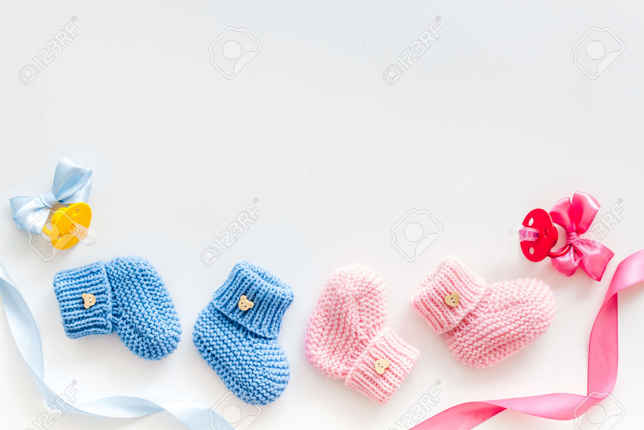 Blue and pink knitted footwear with dummy for baby boy and girl on white background top view mock up - 129481038