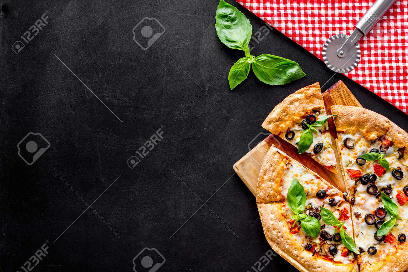Pizza with tomato, basil, olives, cheese on black background top view space for text - 133899328