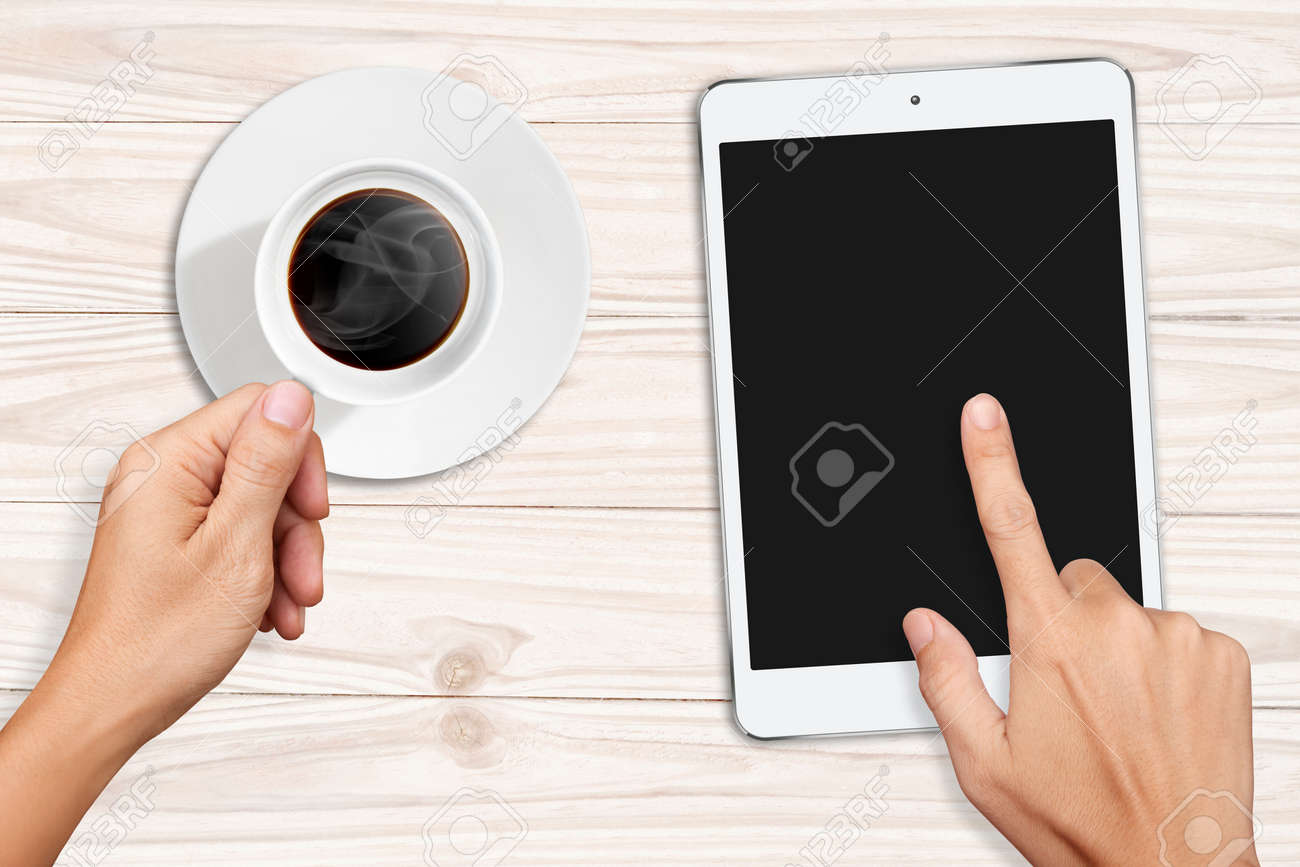 Hands Holding Acup Of Coffee And Touch On Small White Tablet Computer On White  Wooden Table