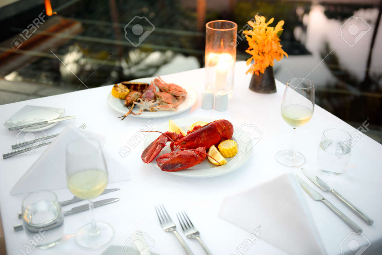 Luxury romantic candle light dinner setup by the pool with plate of lobster and seafood BBQ & Luxury Romantic Candle Light Dinner Setup By The Pool With Plate ...