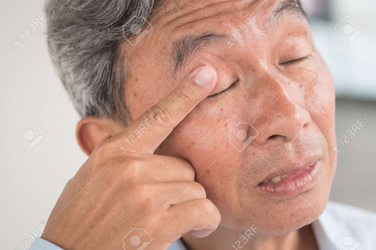 old man with eye irritation optical problem stock photo picture