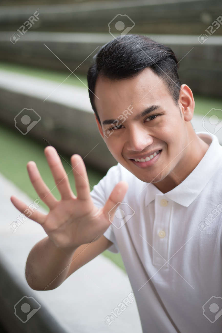 happy man pointing up five finger gesture