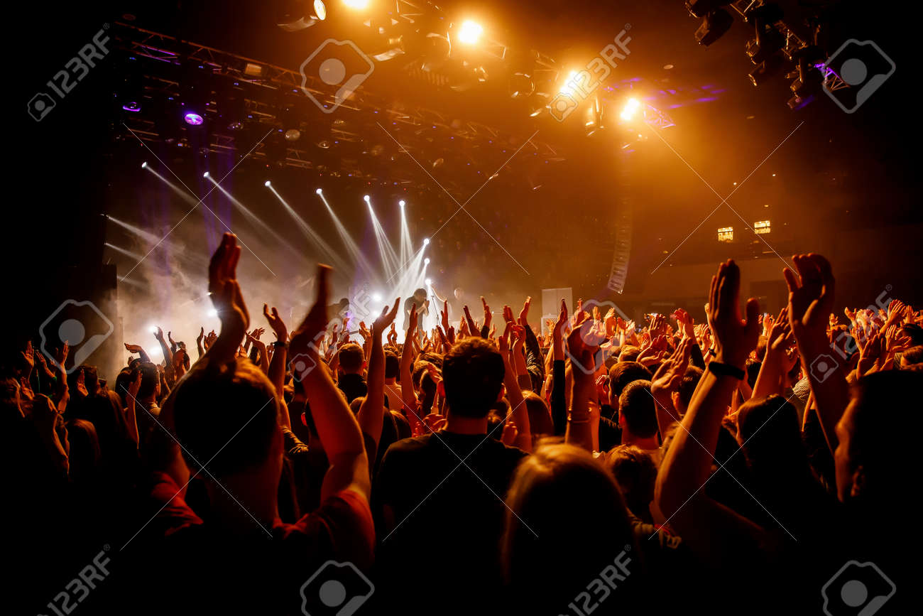 Crowd on music show, happy people with raised hands. Orange stage light - 120665550