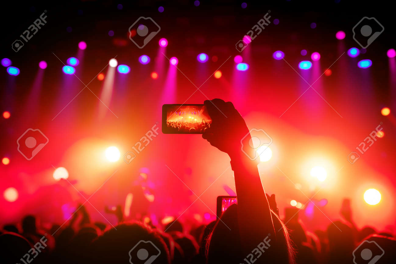 Smartphone in hand at a concert, red light from stage - 120665926