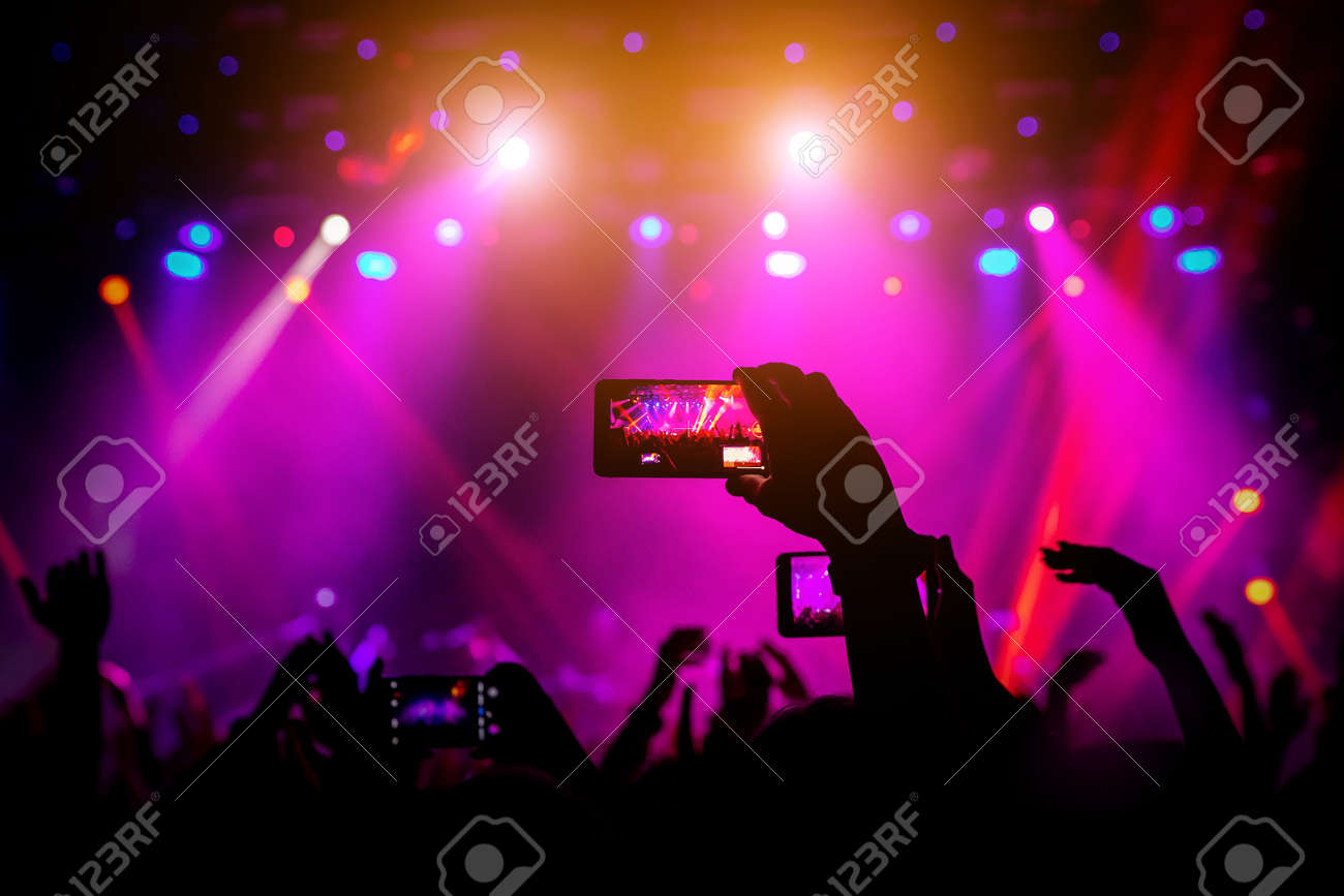 Smartphone in hand at a concert, red light from stage - 120666008