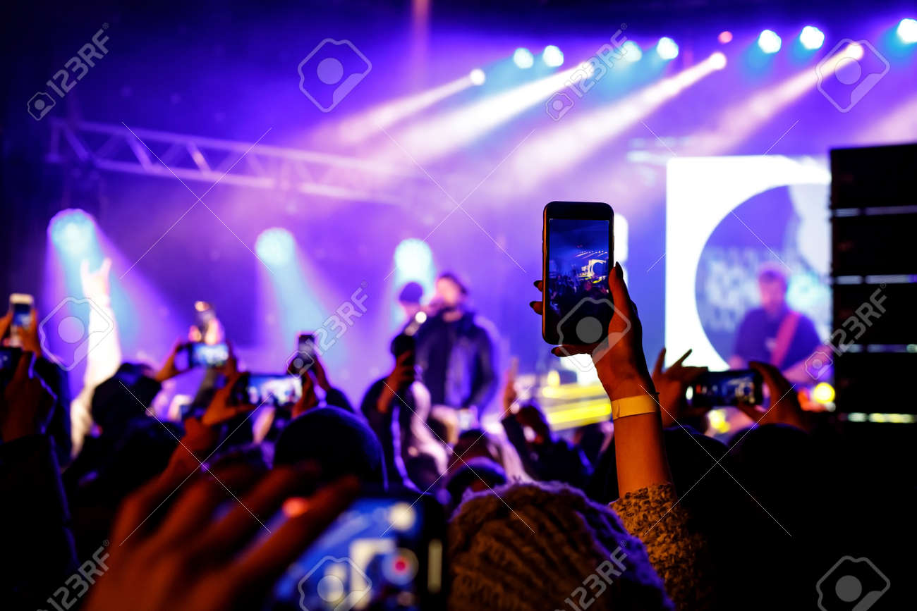 Recording a concert with mobile phone, silhouette of hands with smartphone - 166007438
