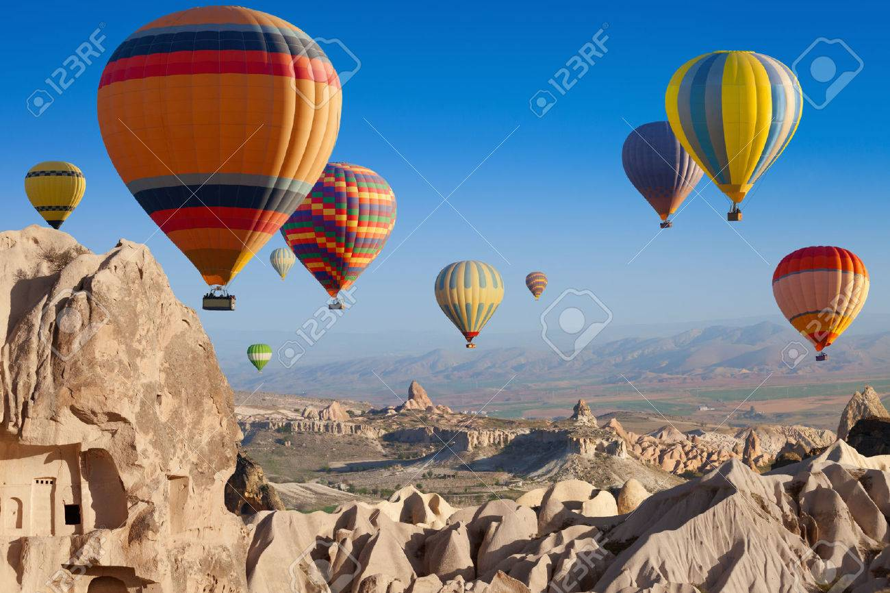 Amazing attraction - hot air balloons flying above unusual rocky landscape in Cappadocia, Turkey - 57744886