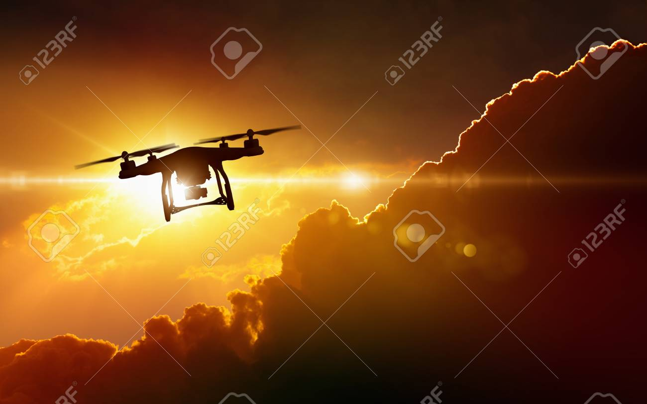 Modern technological background - silhouette of flying drone in glowing red sunset sky - 101721315
