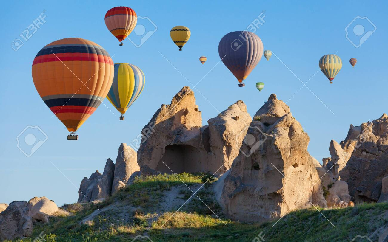 Colorful hot air balloons are flying in clear blue sky above unusual rocky landscape in Cappadocia. Limestone conical rocks with hand carved rooms near Goreme, Cappadocia, Turkey. - 121162474