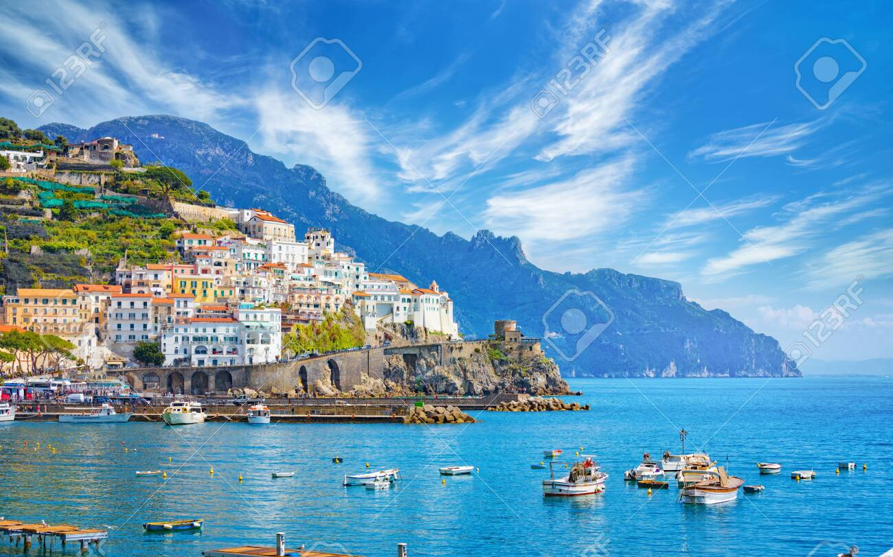 Beautiful Amalfi on hills leading down to coast, comfortable beaches and azure sea in Campania, Italy. Amalfi is most popular travel and holyday destination in Europe. - 126889071