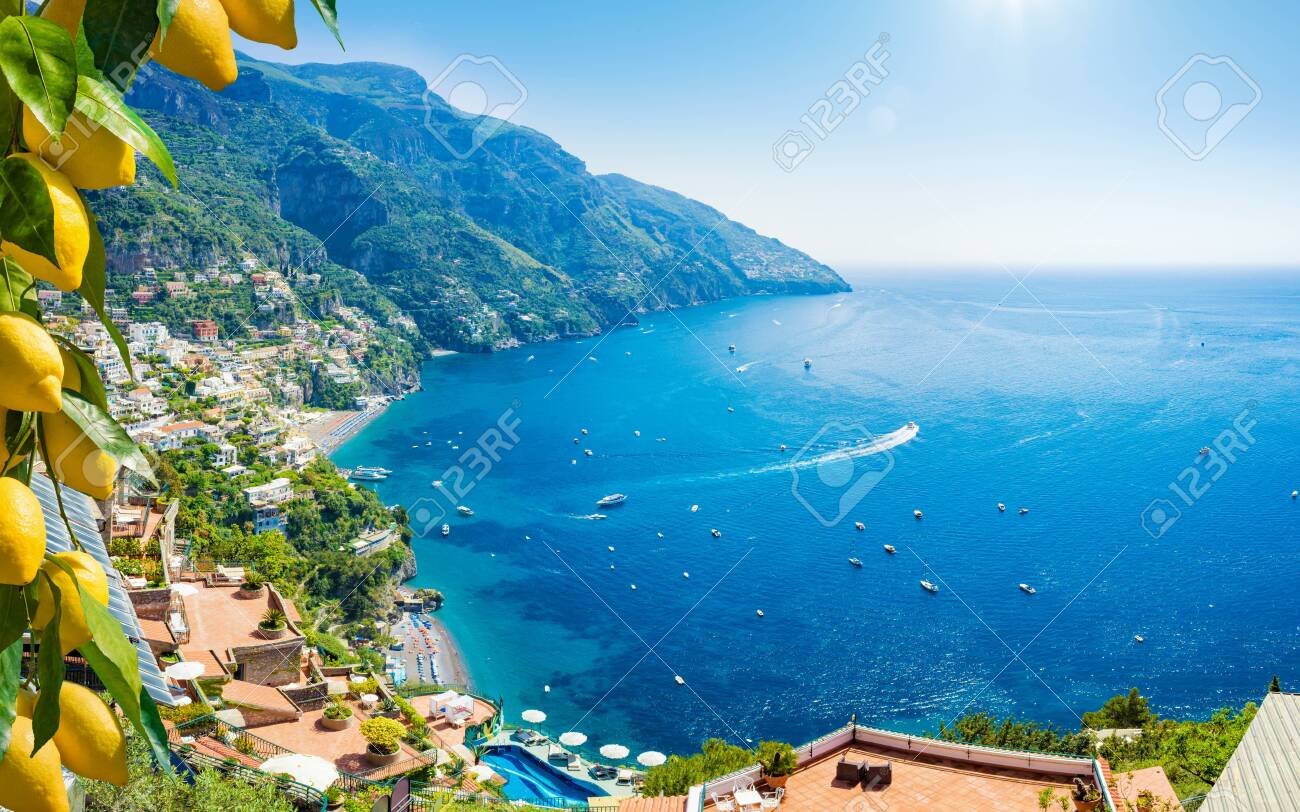 Beautiful Positano with comfortable beaches and clear blue sea on Amalfi Coast in Campania, Italy. Amalfi coast is popular travel and holyday destination in Europe. Ripe yellow lemons in foreground. - 129675699