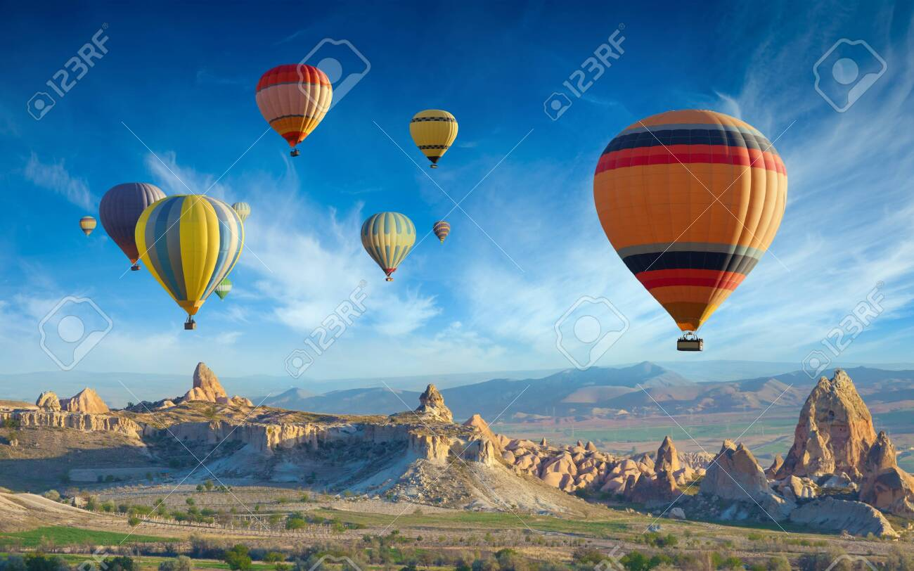 Surise view of unusual rocky landscape in Cappadocia, Turkey. Colorful hot air balloons fly in blue sky over amazing valleys with fairy chimneys in Cappadocia. - 135140090