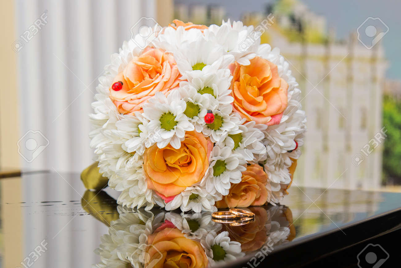 Two Beautiful Wedding Rings And A Wedding Bouquet Of Orange Roses